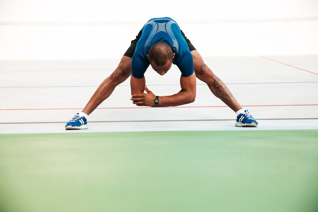 Retrato de corpo inteiro de um jovem desportista fazendo alongamento