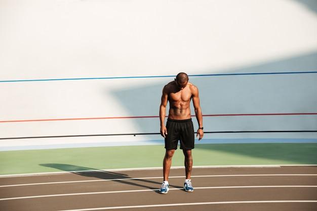 Retrato de corpo inteiro de um jovem desportista muscular