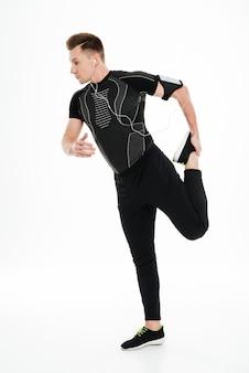 Retrato de corpo inteiro de um jovem desportista saudável, esticando as pernas