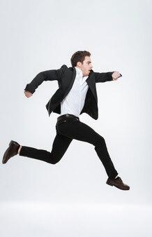 Retrato de corpo inteiro de um jovem empresário atraente pulando e olhando para a frente, isolado em uma parede branca