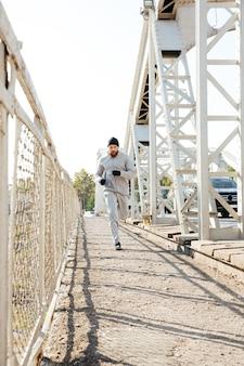 Retrato de corpo inteiro de um jovem esportista concentrado correndo pela ponte ao ar livre