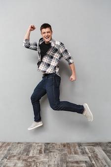 Retrato de corpo inteiro de um jovem feliz pulando