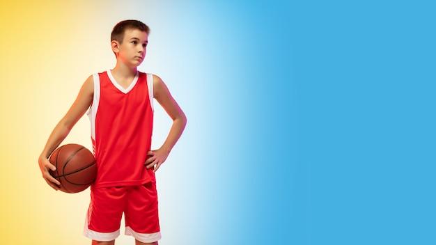 Retrato de corpo inteiro de um jovem jogador de basquete com uma bola em fundo gradiente