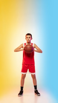 Retrato de corpo inteiro de um jovem jogador de basquete com uma bola na parede gradiente