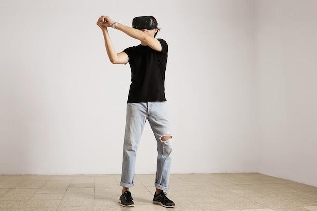 Retrato de corpo inteiro de um jovem modelo caucasiano em jeans rasgados azuis claros e camiseta preta jogando beisebol ou tênis com óculos de realidade virtual