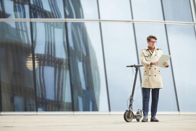 Retrato de corpo inteiro de um jovem moderno vestindo sobretudo e lendo documento enquanto se inclina em uma scooter elétrica em um ambiente urbano de cidade com edifícios de vidro no fundo, copie o espaço