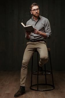 Retrato de corpo inteiro de um jovem pensativo em óculos, sentado na cadeira e lendo um livro isolado em uma superfície de madeira preta