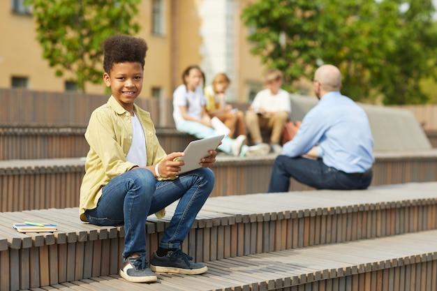 Retrato de corpo inteiro de um menino afro-americano sorridente, olhando para a câmera enquanto está sentado no banco ao ar livre com a professora dando aula no fundo, copie o espaço