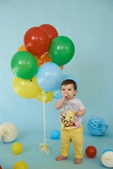 Retrato de corpo inteiro de um menino alegre segurando balons posando contra um fundo azul, conceito de festa de aniversário
