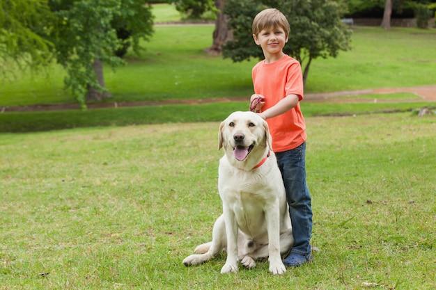 Retrato de corpo inteiro de um menino com cachorro no parque