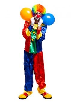 Retrato de corpo inteiro de um palhaço masculino em traje segurando um monte de balões isolados no fundo branco