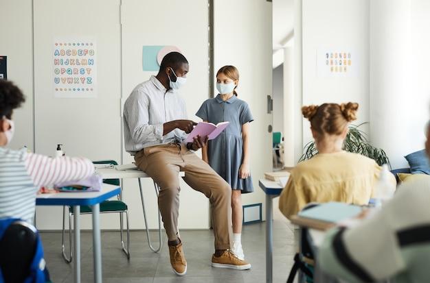Retrato de corpo inteiro de um professor afro-americano usando máscara na sala de aula da escola, medidas de segurança ambiciosas, copie o espaço