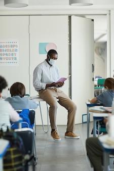 Retrato de corpo inteiro de um professor afro-americano usando máscara na sala de aula da escola, medidas de segurança ambiciosas