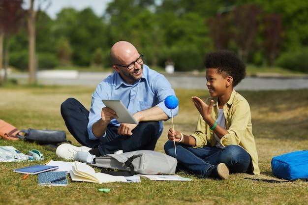 Retrato de corpo inteiro de um professor careca sorridente conversando com um garoto afro-americano segurando um planeta modelo enquanto desfruta de uma aula de astronomia ao ar livre sob a luz do sol, copie o espaço
