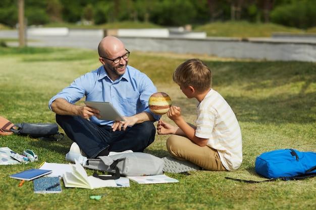 Retrato de corpo inteiro de um professor careca sorridente falando com um adolescente segurando o planeta modelo enquanto desfruta de uma aula de astronomia ao ar livre sob a luz do sol, copie o espaço