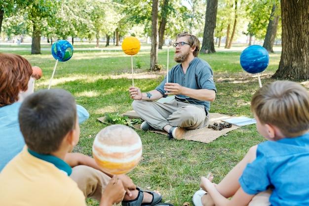 Retrato de corpo inteiro de um professor falando com um grupo de crianças enquanto está sentado na grama verde e aproveitando a aula ao ar livre sob a luz do sol