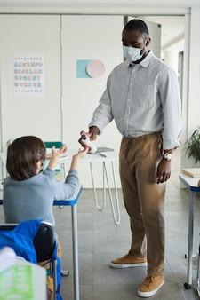 Retrato de corpo inteiro de um professor higienizando as mãos de crianças na sala de aula, medidas de segurança ambiciosas