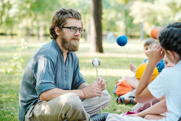Retrato de corpo inteiro de um professor sorridente falando com as crianças enquanto está sentado na grama verde e aproveitando a aula ao ar livre sob a luz do sol