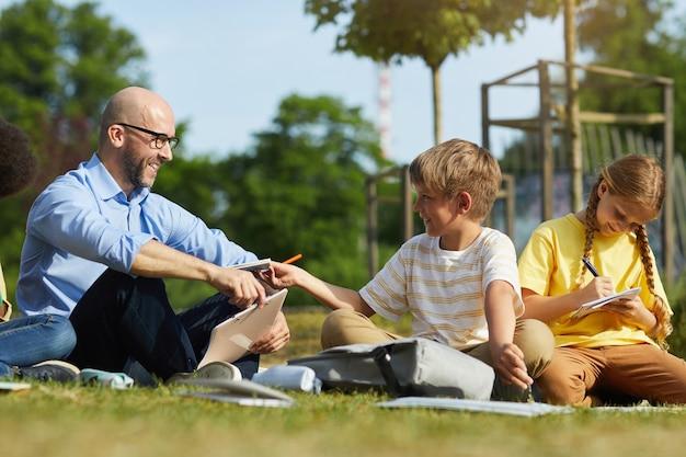 Retrato de corpo inteiro de um professor sorridente falando com um adolescente sentado na grama verde e aproveitando a aula ao ar livre.