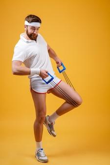 Retrato de corpo inteiro de um treino de homem fitness com expansor