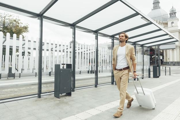 Retrato de corpo inteiro de um viajante masculino vestindo um terno elegante, andando na estação pública com uma mala branca