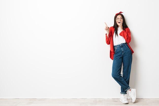 Retrato de corpo inteiro de uma adolescente animada e fofa vestindo roupa casual, isolado na parede branca, apresentando espaço de cópia
