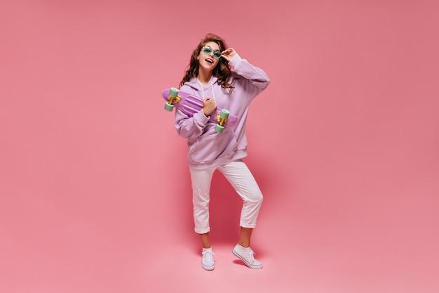 Retrato de corpo inteiro de uma adolescente elegante com capuz roxo e calça branca tirando os óculos de sol verdes