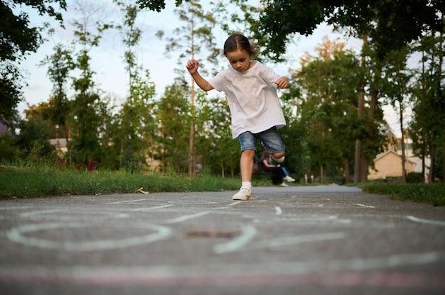 Retrato de corpo inteiro de uma adorável menina jogando amarelinha no chão de um parque da cidade em um lindo dia quente de verão ao pôr do sol. jogos infantis de rua em clássicos.