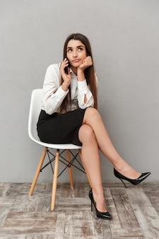 Retrato de corpo inteiro de uma adorável mulher com longos cabelos castanhos no trabalho de negócios, sentado na cadeira com uma aparência chata e tendo uma conversa móvel, isolado sobre a parede cinza