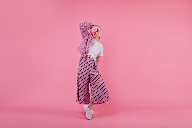 Retrato de corpo inteiro de uma adorável mulher europeia usa calça listrada rosa e jaqueta de pele durante a sessão de fotos. garota refinada com cabelo curto e colorido posando com roupas da moda