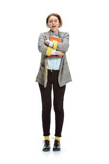 Retrato de corpo inteiro de uma aluna surpresa segurando livros isolados no espaço em branco
