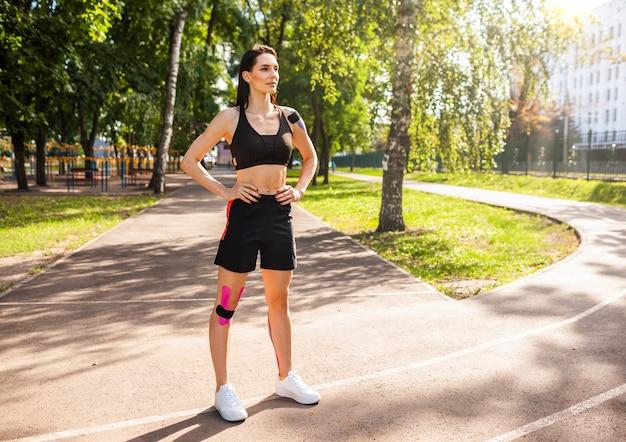 Retrato de corpo inteiro de uma atraente mulher morena musculosa, vestindo roupa esportiva preta, posando ao ar livre