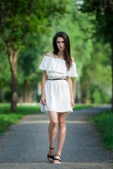 Retrato de corpo inteiro de uma bela jovem em um vestido branco com ombros abertos, pele limpa, cabelo comprido e maquiagem casual