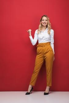 Retrato de corpo inteiro de uma bela jovem empresária em pé sobre um fundo vermelho, apontando para longe