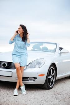 Retrato de corpo inteiro de uma bela jovem falando no smartphone e em frente ao carro