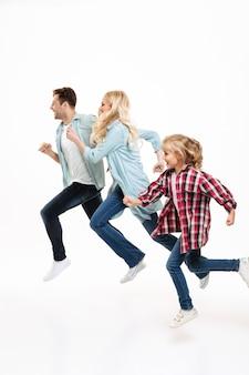 Retrato de corpo inteiro de uma bela jovem família correndo
