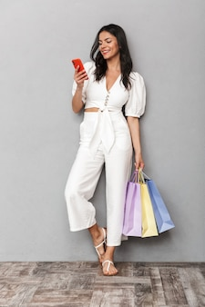 Retrato de corpo inteiro de uma bela jovem morena vestindo roupa de verão, em pé, isolado na parede cinza, carregando sacolas de compras, usando telefone celular