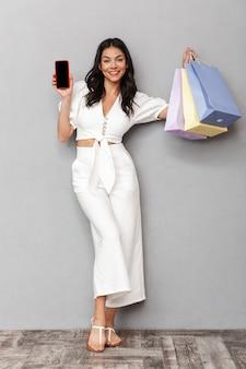Retrato de corpo inteiro de uma bela jovem morena vestindo roupa de verão, isolada na parede cinza, carregando sacolas de compras, mostrando o celular com tela de blak