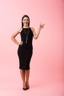 Retrato de corpo inteiro de uma bela jovem usando um vestido preto em pé isolado sobre um fundo rosa, apontando para o espaço da cópia