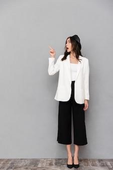 Retrato de corpo inteiro de uma bela jovem vestida com jaqueta e calça em pé sobre um fundo cinza, apontando o dedo para longe