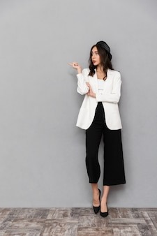 Retrato de corpo inteiro de uma bela jovem vestida com jaqueta e calça em pé sobre um fundo cinza, apontando para o lado oposto