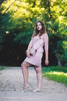 Retrato de corpo inteiro de uma bela modelo plus size em vestido rosa, jovem ao ar livre na natureza