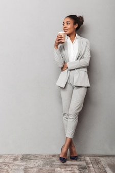 Retrato de corpo inteiro de uma confiante mulher de negócios na áfrica, vestindo um terno de pé, segurando uma xícara de café para viagem