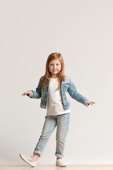 Retrato de corpo inteiro de uma criança fofa com roupas jeans elegantes, olhando para a câmera e sorrindo