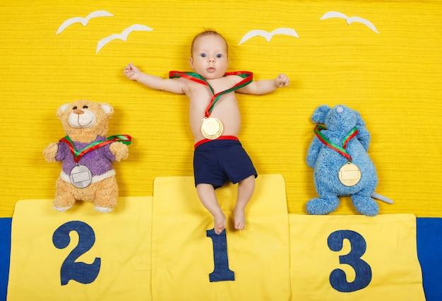 Retrato de corpo inteiro de uma criança pequena está de pé em um pódio de lugar em primeiro lugar.