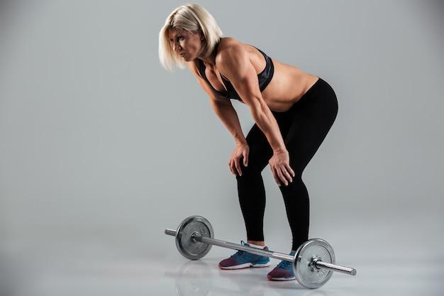 Retrato de corpo inteiro de uma desportista adulta muscular exausta