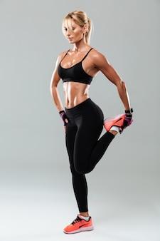 Retrato de corpo inteiro de uma desportista bonita fazendo exercícios de alongamento