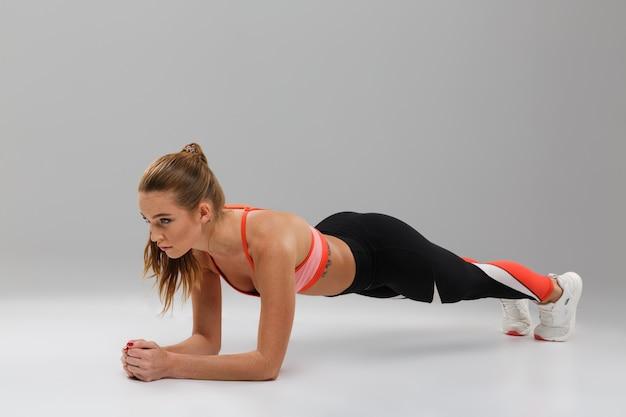 Retrato de corpo inteiro de uma desportista em boa forma fazendo prancha