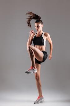 Retrato de corpo inteiro de uma desportista em forma concentrada
