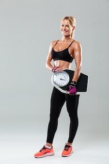 Retrato de corpo inteiro de uma desportista em pé e segurando pesos